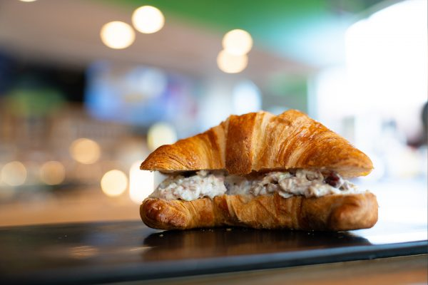 lunch is served with a chicken salad sandwich on a fresh baked croissant