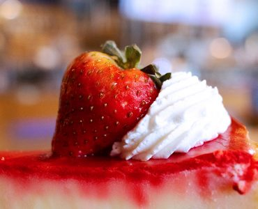 cheesecake with fresh strawberries and whipped cream that redirects to our dessert menu